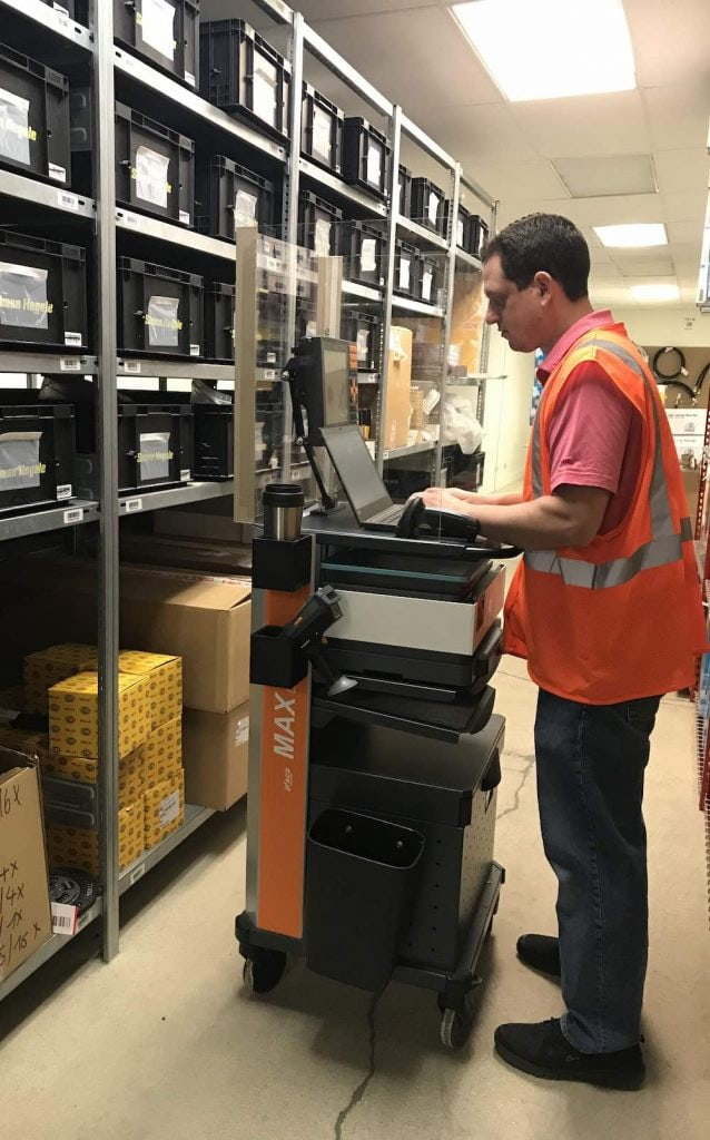 Employee using MAX Mobile Workstation with Covid screen to pick orders